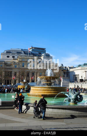 Fountains and tourists with Canada House on the far side, Trafalgar Square, London, England, UK - Stock Photo