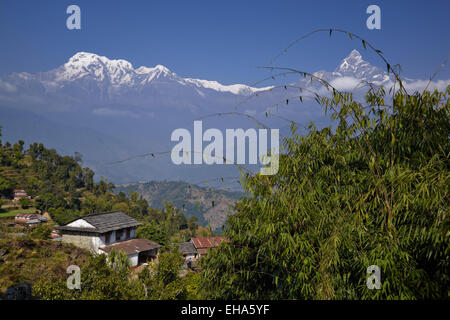 Traditional Gurung house with the Annapurnas in the background - Stock Photo