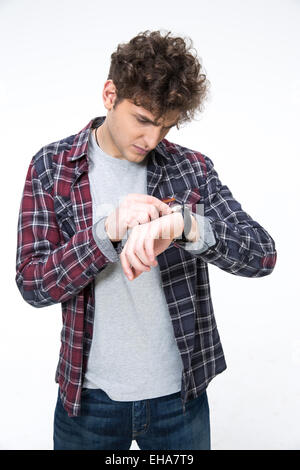 Casual man looking on the watch over gray background - Stock Photo