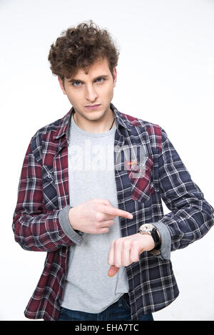 Angry young man pointing on the wristwatch - Stock Photo
