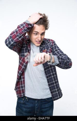 Young man looking on the watch over gray background - Stock Photo