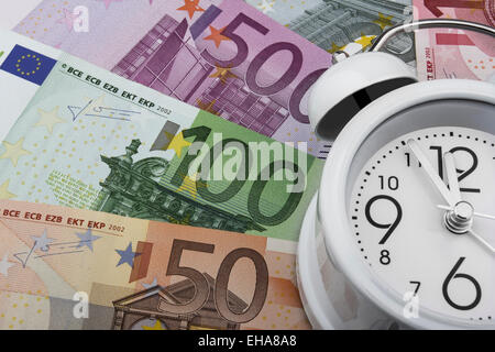 Euro notes and a clock. Time is money. (50, 100 and 500 EUR)