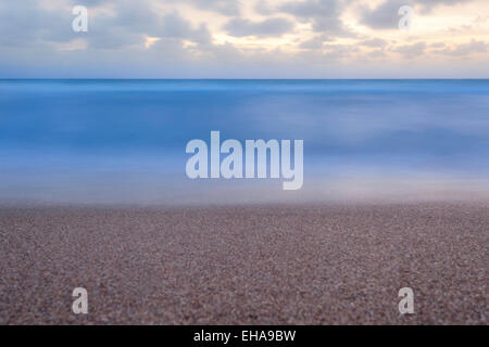 Minimalist view from the Florida beach of a flat calm ocean at sunrise with fluffy clouds in the sky. - Stock Photo