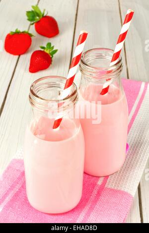 Strawberry milk in traditional bottles with straws on white wood table - Stock Photo