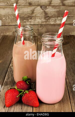 Strawberry and chocolate milk in traditional bottles with straws on old wood background - Stock Photo