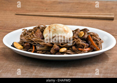 Traditional Chinese tea egg served on a nest of stir fried soba noodles with pork, oyster mushroom and peanuts. - Stock Photo