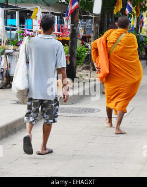 People pray with monk and put food offerings to Buddhist alms bowl in morning time at small market at Bangkok, Thailand. - Stock Photo