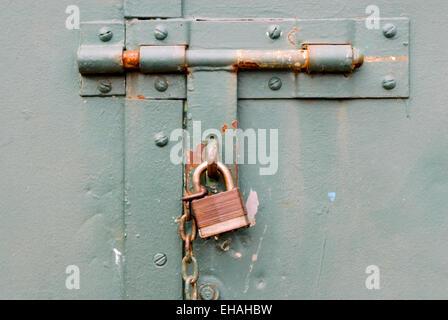Closed rusted padlock blocking deadbolt on green steel door. - Stock Photo
