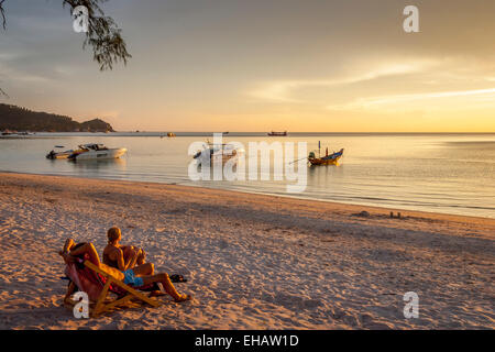 A Couple Watch The Sunset On Hat Sairee Beach, Ko Tao, Thailand - Stock Photo