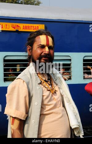 A Vishnu devotee  Sadhu Indian Holy man standing on the platform of Delhi Railway Station with a train in the background - Stock Photo