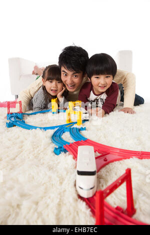The father and two children and play cars in the living room - Stock Photo