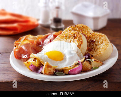 Full English Breakfast with crumpets, served on a white plate in a table setting - Fried egg, bacon, sautéed potatoes - Stock Photo