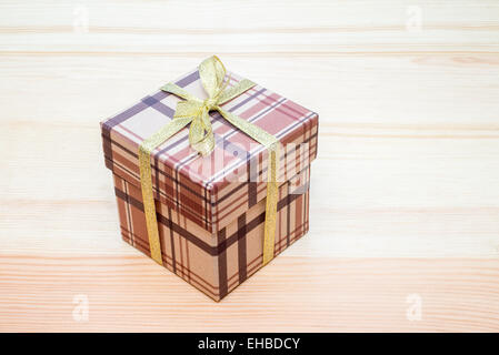 brown gift box with bow on wooden table - Stock Photo
