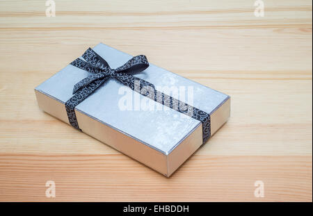 silver gift box with bow on wooden table - Stock Photo