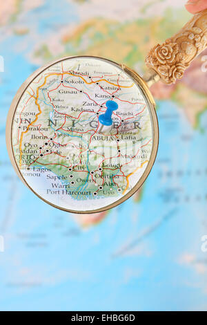 Blue tack on map of Africa with magnifying glass looking in on Abuja,Nigeria - Stock Photo
