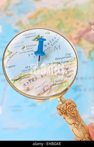 Blue tack on map of Africa with magnifying glass looking in on Algiers, Algeria - Stock Photo