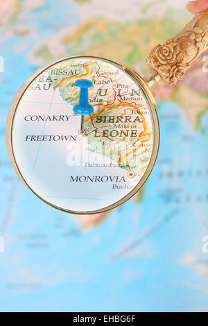 Blue tack on map of Africa with magnifying glass looking in on Freetown, Sierra Leone - Stock Photo
