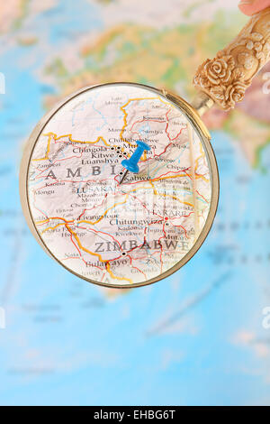 Blue tack on map of Africa with magnifying glass looking in on Lusaka, Zambia - Stock Photo