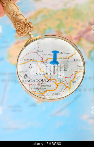 Blue tack on map of Africa with magnifying glass looking in on Niamey, Niger - Stock Photo