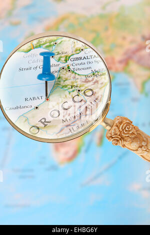Blue tack on map of Africa with magnifying glass looking in on Rabat, Morocco, - Stock Photo
