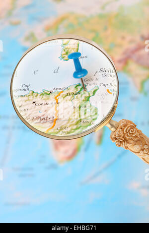 Blue tack on map of Africa with magnifying glass looking in on Tunis, Tunisia - Stock Photo