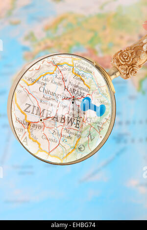 Blue tack on map of Africa with magnifying glass looking in on Harare, Zimbabwe, - Stock Photo