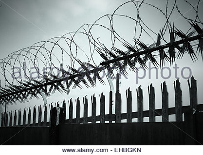 Security barbed razor wire and spiked fencing against sky - Stock Photo