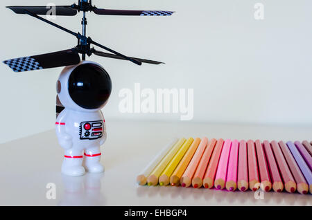 A child's toy spaceman looks towards a set of coloring crayons laid in a row on a white surface. There is some reflected detail.
