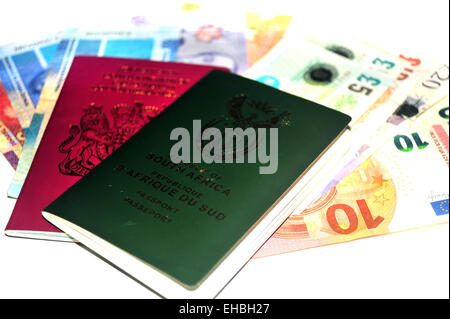 British and South African passports full of money photographed in a studio against a white background. - Stock Photo