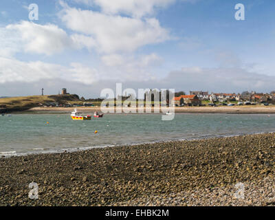 View across North Sea to Lindisfarne Abbey ruins and houses on Holy Island Northumberland England UK on lovely March - Stock Photo