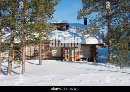 A log cabin  in Levi Lapland Finland with snow and winter sunshine.  Used as winter holiday accommodation. - Stock Photo