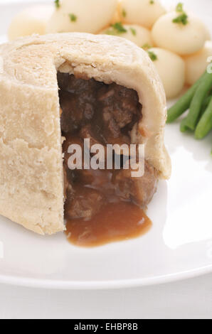 Steak and kidney pudding a traditional steamed suet pastry pie served with new potatoes and green beans - Stock Photo