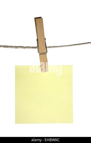 sticky note hanging on a peg from a line - Stock Photo