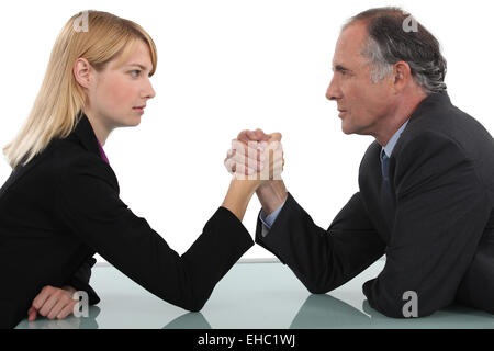 Businessman and woman arm wrestling - Stock Photo