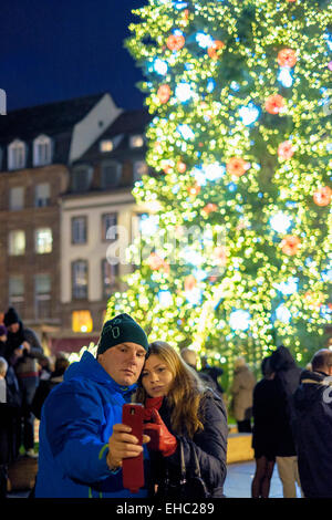 Couple taking selfie photograph in front of giant illuminated Christmas tree, Place Kléber square,  Strasbourg Alsace - Stock Photo