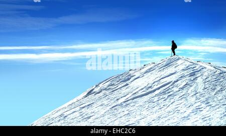 Climber on top of the mountain contemplating nature  Man on the mountain top with snow and blue sky. - Stock Photo