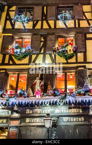 Restaurant's facade decorated at night on Christmas time Strasbourg Alsace France - Stock Photo