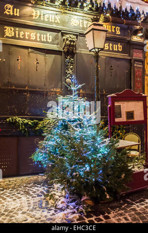 Snowy fir tree in front of 'Au Vieux Strasbourg' closed restaurant at night on Christmas time Strasbourg Alsace - Stock Photo