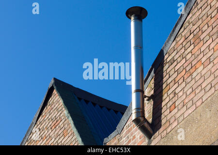 Stainless Steel Industrial Chimney on a Factory Wall, UK - Stock Photo