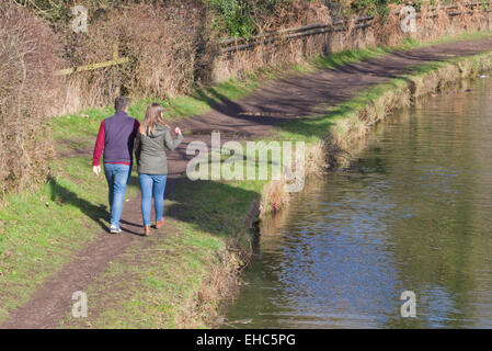 Young Caucasian Couple Waliking Along Stourbridge Canal Towpath, Staffordshire, England, UK in Winter - Stock Photo