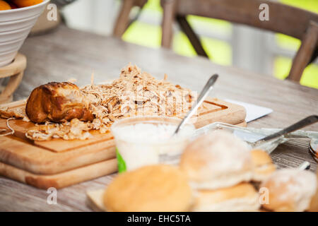 Pulled Pork meat on a chopping board ready for eating - Stock Photo