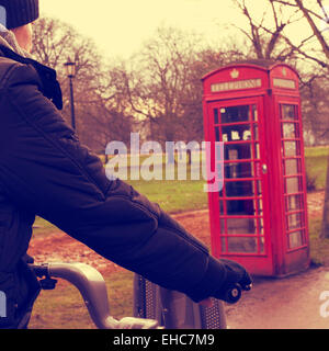 a young man riding a bicycle in Hyde Park in winter in London, United Kingdom, with a typical red telephone booth - Stock Photo
