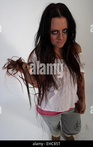 young woman with scars on arm from self-harm, and tearing off her hair - Stock Photo