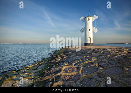 Sunrise on the coast, lighthouse windmill in Swinoujscie, Poland. - Stock Photo