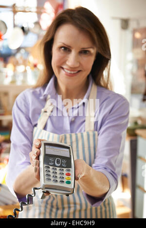 Sales Assistant In Homeware Store With Credit Card Machine - Stock Photo