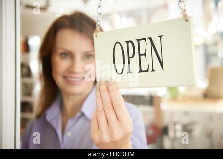Store Owner Turning Open Sign In Shop Doorway - Stock Photo