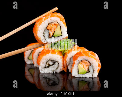 Delicious sushi rolls served on black table with chopsticks - Stock Photo
