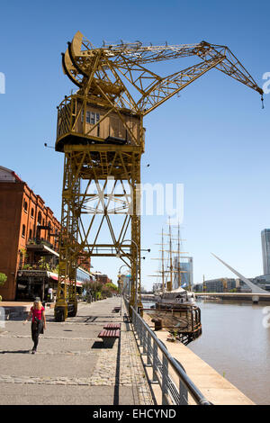 Argentina, Buenos Aires, Puerto Madero, crane beside quayside restaurants in old warehouses - Stock Photo