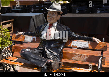 Argentina, Buenos Aires, Puerto Madero, quayside sculpture of well-dressed man sat on bench in sunshine - Stock Photo