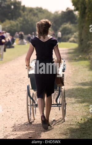 Young woman pushes a pram with baby in 1950's style clothes around the motor circuit at the 2014 Goodwood Revival, - Stock Photo